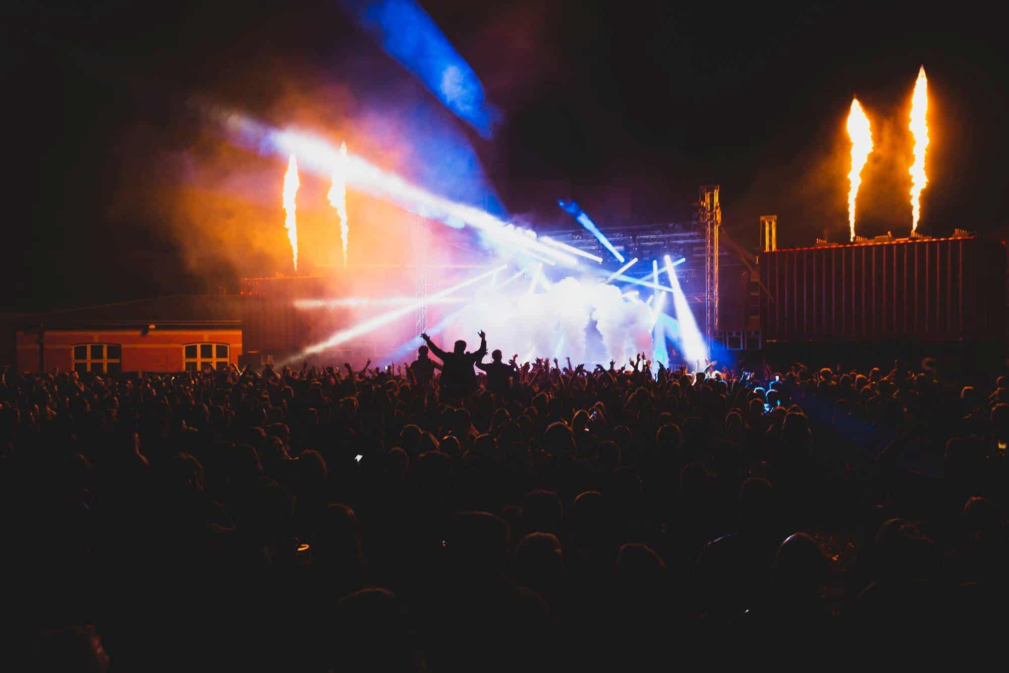 Folk der fester i orange lys og røg til Generator 2018